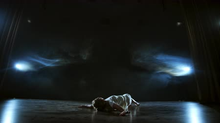 lelkesedés : Modern ballet dancing woman barefoot lying on the floor doing spins and pirouettes and somersaults Stock mozgókép
