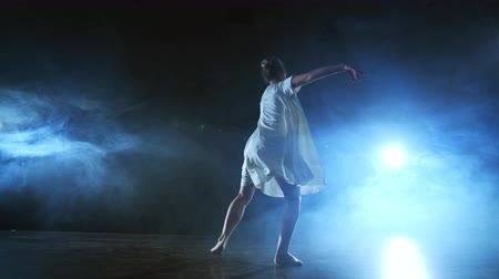entusiasmo : Modern ballet dancing woman barefoot doing spins and pirouettes and dance steps standing on stage in smoke in slow motion. Performance on stage