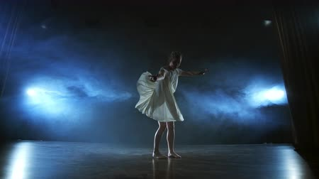 アジリティ : Modern ballet dancing woman barefoot doing spins and pirouettes and dance steps standing on stage in smoke in slow motion. Performance on stage