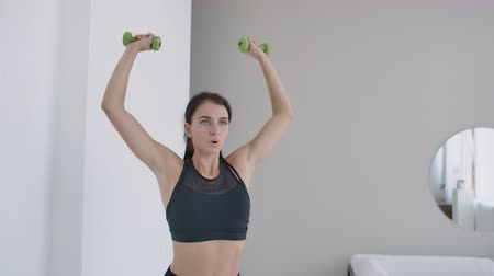 head over : Raise the dumbbells over your head performing exercises for the shoulders. Training at home in the apartment