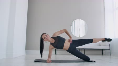 воля : The brunette in the apartment does an exercise lateral plank standing on her knee and raising her leg up. Fitness marathon