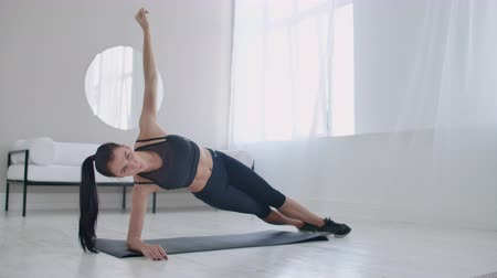 воля : The brunette in the apartment does an exercise plank while standing in a static position on the lateral muscles of the abs and moving her hand up and down.