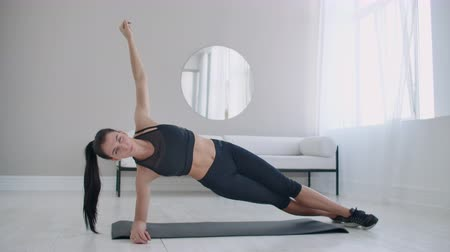 türelem : The brunette in the apartment does an exercise plank while standing in a static position on the lateral muscles of the abs and moving her hand up and down.