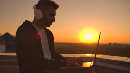 ouvir : Rear view of a man in headphones listening to music and working on the roof of a building at sunset with a view of the city from a height. Roof of a skyscraper at sunset