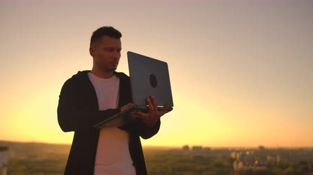 hacker computer : A man with a laptop at sunset stands on the roof of the building and writes a code on the keyboard. Hacker with laptop Stock Footage