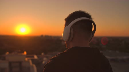 senha : The camera is tracking a man walks on the roof at sunset with headphones looking at the city from the height of a skyscraper at sunset. Relax while listening to music. Vídeos