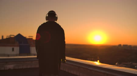 contraseña : A man walks on the roof at sunset with headphones looking at the city from the height of a skyscraper at sunset. Relax while listening to music.