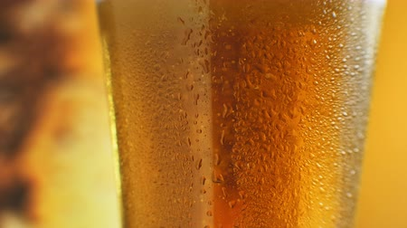 ale : Macro Shot Of Fine Bubbles Rising In A Glass With Orange Liquid. Cold Light Beer in a glass with water drops. Craft Beer close up. Rotation 360 degrees