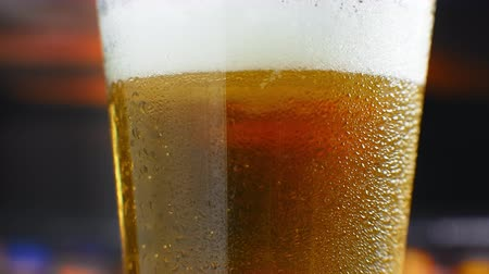 fabricado cerveja : Close-up slow motion: cold Beer in a glass large drops and bubbles in the beer.