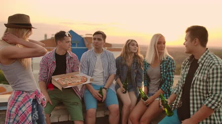 friendship dance : The company of six young people communicate with each other on the roof with pizza and beer. Girls look around at summer sunset.