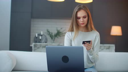 легкий : A blonde in a sweater sits at home on the couch with a laptop looking at the screen and holding a credit card and typing on the keyboard Стоковые видеозаписи