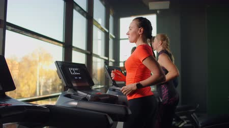 treadmill : Cute young girl running on a treadmill in front of panoramic Windows in the fitness room. Gym with treadmill and large Windows