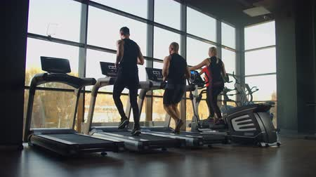 cardio workout : A group of people running on a treadmill in a fitness room performing a cardio workout. Men and women train together Running indoors, warm-up before training in slow motion