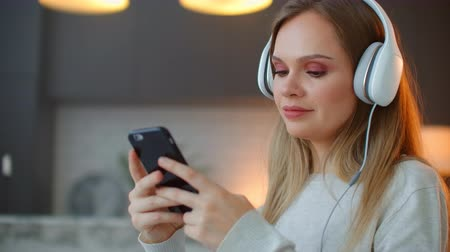 dal : Calm happy young woman in headphones chilling sitting on sofa with eyes closed listening to favorite music holding phone using mobile online player app enjoy peaceful mood wearing earphones
