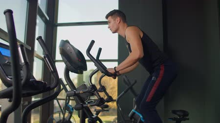 sollevamento pesi : Beautiful fit sportive positive young man in gym doing exercises on elliptical trainer working out. Hard