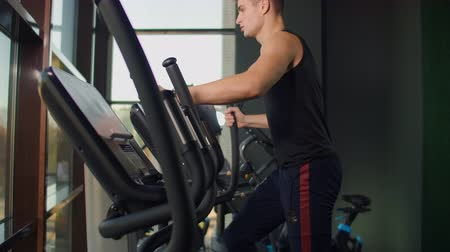 sollevamento pesi : Portrait fitness man warm up before training on elliptical cross trainer in gym club. Close-up male training cardio exercise on cross trainer in fitness.