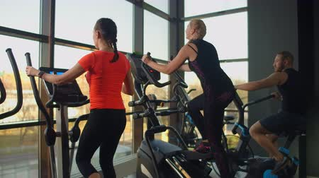 elliptical : Young fit woman using an elliptic trainer in a fitness center. A group of young women train on sports training equipment in a fitness gym. Steady cam shot.