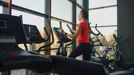 sollevamento pesi : Beautiful fit sportive positive young woman in gym doing exercises on elliptical trainer working out. Slow motion, the woman on the elliptical trainer Filmati Stock
