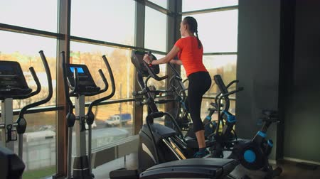 elliptical : Cute young brunette doing thigh exercises on the simulator. Modern simulators near the panoramic window