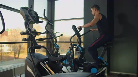 инструктор : Fit young men using air bike at the gym. Strong male athlete doing cardio workout on cycle at health club.