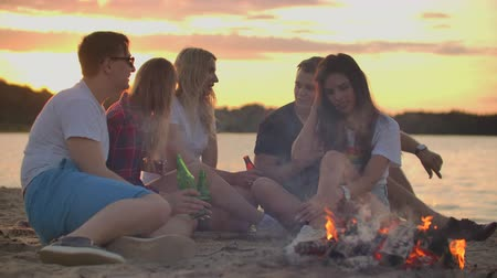 bodywarmer : Young people are enjoying warm summer evening on the sand beach Stockvideo