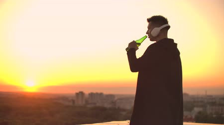 антивирус : A man drinks beer standing on the roof and contemplates the world. Look at the view of the city at sunset from a height. The roof of a skyscraper