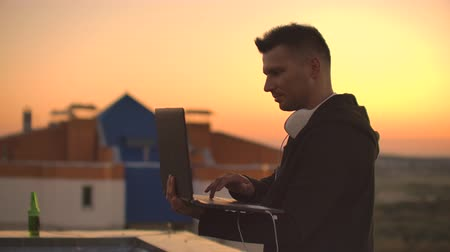 антивирус : A young man sitting on the edge of the roof with a laptop and a beer, working typing on a laptop. Стоковые видеозаписи