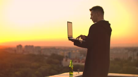 contraseña : Standing at sunset on the roof with a laptop and a beer. A man in a hoodie works having fun and contemplating the beauty of the city view from a height Archivo de Video