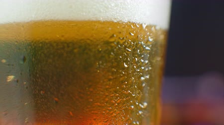 fabricado cerveja : Macro shot of a beer glass with cold beer, bubbles rise in the glass. Slow motion beer bubbles. Stock Footage