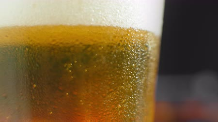 fabricado cerveja : Macro shot of a beer glass with cold beer, bubbles rise in the glass. Slow motion beer bubbles. Vídeos