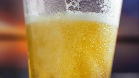 microbrewery : slow-motion Macro cold beer is poured into a glass with perspiration. Beer bubbles rise to the surface Stock Footage