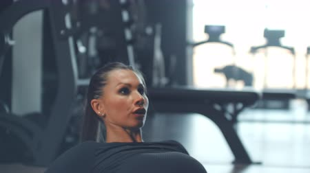 břišní : Highly motivaited girl is doing abs training in the Gym with large Windows on the background of a running man on a treadmill Dostupné videozáznamy