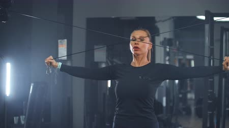 willpower : The girl shakes the muscles of the chest and arms in the gym