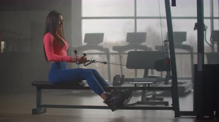 buikspieren : A woman sitting pulls the weight of a simulator against the backdrop of large Windows and treadmills of the gym. Power training on special training machine in fitness center