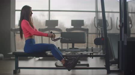 muscular build : Intensive power training in gym. A woman sitting pulls the weight of a simulator against the backdrop of large Windows and treadmills of the gym