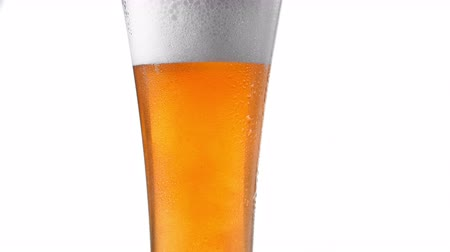 fabricado cerveja : Close up background white of with bubbles beer in glass, low angle side view, slow motion.