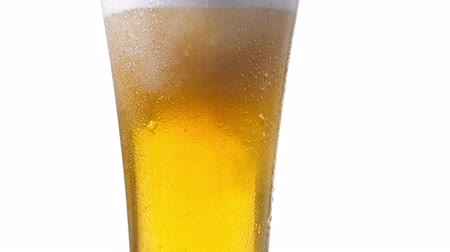 ale : Pouring yellow beer on white background. Barm, bubble fresh drinking, foamy golden alcohol. Stock Footage