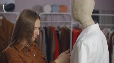 manekin : A young brunette looks at a clothing store dressed on a mannequin. Clothing store in the supermarket. Brand clothing in a boutique girl looks at a mannequin.