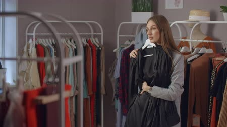 dressing room : A young Brunette in a Clothing Store Chooses a Dress to hang on a Hanger and Tries it on. Buy a dress in the store. Search and choose clothes in a boutique.