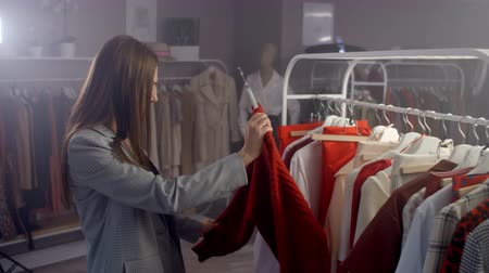 pitka : A young Brunette in a Clothing Store Chooses a Dress to hang on a Hanger and Tries it on. Buy a dress in the store. Search and choose clothes in a boutique.