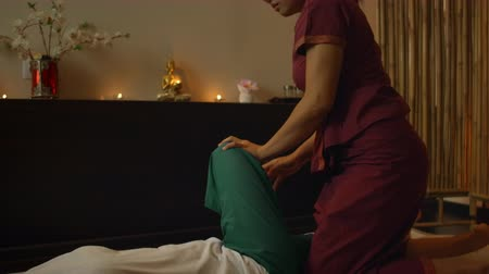 preparált : Asian Woman performs Traditional Thai Massage to beautiful European Woman. Rehabilitation and Treatment after Injuries with the help of Massage. Relax and Rest from massage of Legs, Arms and Back.