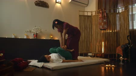 fysiotherapeut : Asian Woman performs Traditional Thai Massage to beautiful European Woman. Rehabilitation and Treatment after Injuries with the help of Massage. Relax and Rest from massage of Legs, Arms and Back.