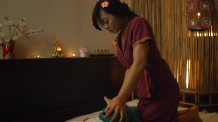 なだめる : Thai massage. The asian woman rubbed by traditional chiropractor on his back with the hands to relieve tension or pain.