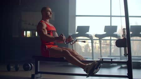 тянуть : a tired sporty man sitting on the indoor rower at gym. people and fitness concept Стоковые видеозаписи