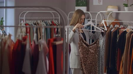 dressing room : shopping, fashion, style and people concept - happy woman choosing clothes and looking to mirror in mall or clothing store.