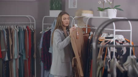 pitka : shopping, fashion, style and people concept - happy woman choosing clothes and looking to mirror in mall or clothing store.