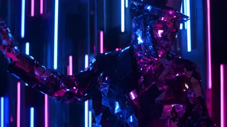 különc : A man dances in neon light in a glass suit. Shiny sparkling silver suit, and blue purple neon light. New year party.
