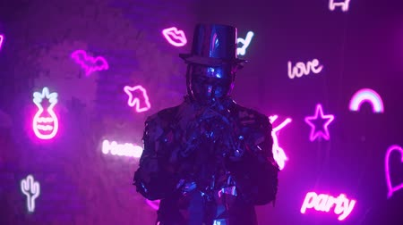 výstřední : A man dances in neon light in a glass suit. Shiny sparkling silver suit, and blue purple neon light. New year party.
