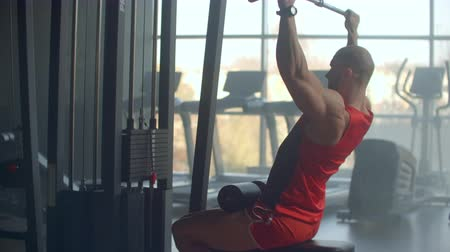 resistência : Athlete doing exercises in the simulator with weights and pulls the bar sitting on the background of a large window GYM. Strong purposeful athlete view from the back.