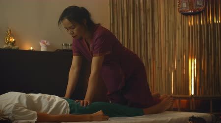 протирать : An Asian woman performs a traditional Thai massage on the back of a lying beautiful European girl. Chiropractor produces treatment with alternative methods